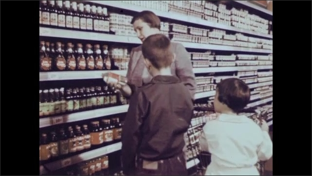 1950s: Measuring cup. Carton of milk. Woman and children in grocery store. Woman hands glass jug to boy. Boy places glass jug in grocery cart.