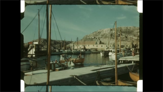 1950s: Fishing boat goes by in water. Fishing boats at docks in village. Small boat pulls up to docks. People on docks.