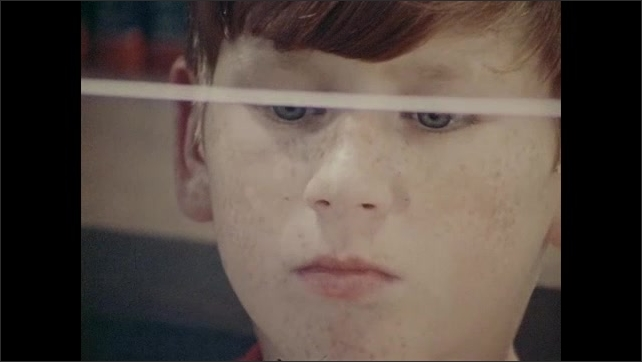 1970s: Boy holds up transparent sheet. Boy looking through sheet. Close up of boy, zoom out, boy holding pane of glass.