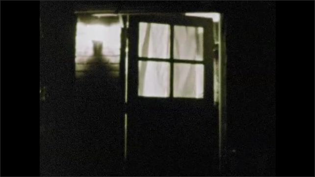 1960s: Night shot, man by fire, picks up flashlight. Man walking with flashlight. Man walks to house, enters door. Outdoor light on house. Paper burning in wastebasket. Car pulls into driveway.