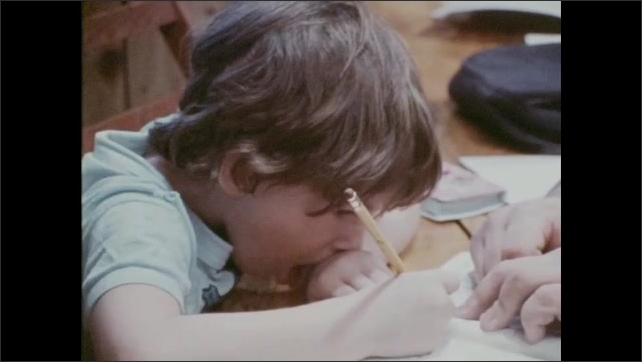 1970s: Man and girl at table, man points to notebook. Close up of man, pan to girl writing. Hands cooking meat, tilt up to man cooking. Man sits at table, cuts onion.