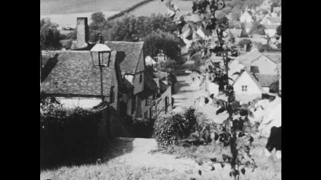 1950s: boy carries pile of wool down stairs to village, boy with wool enters building, aerial view of village, fields and trees, woman at desk looks up, thinks, writes with quill pen