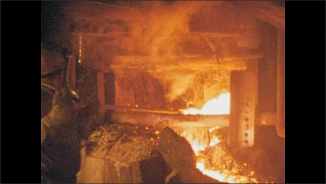 1970s: Men in hardhats working in foundry. Liquid metal poured from furnace.
