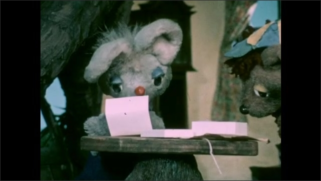 1970s: Puppets.  Tree house.  Mouse and bear look at unwrapped package.  Mouse reads letter.