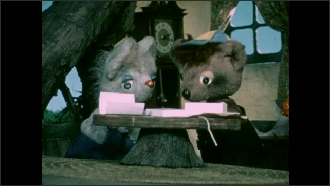 1970s: Puppets.  Monkey delivers groceries to tree house.  Mouse puts grocery bag in chair.  Mouse and bear talk.  Mouse holds scarab beetle.