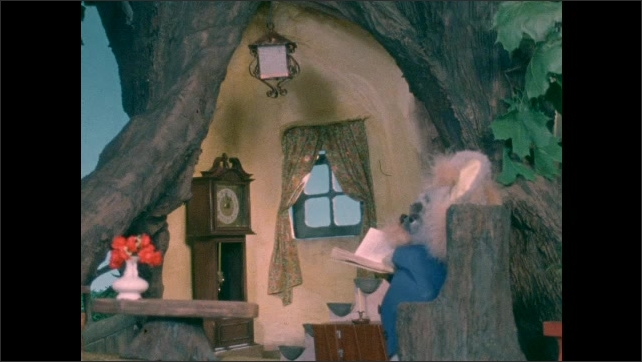 1970s: Mouse puppet sits in chair and reads book. Mouse puppet sits in tree home.