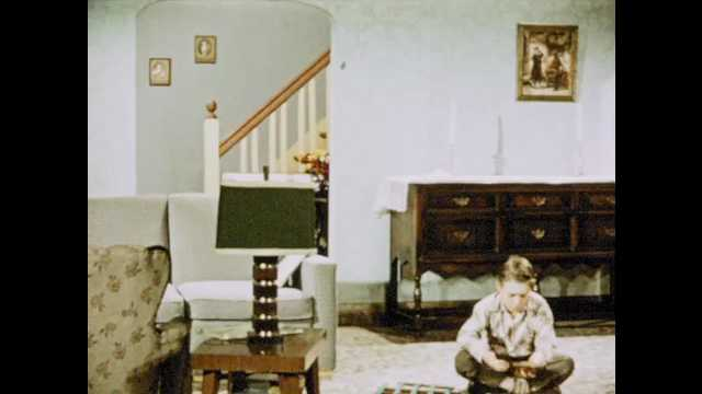1950s: Boy plays on living room floor, teen girl walks down stairs. Girl walks up to man and woman, talks to man. Woman, man, and teen have conversation.