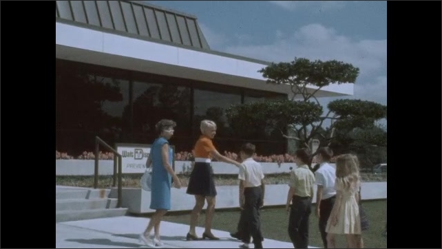 1970s: Exterior of building, man hits clapboard, woman walks down steps, greets woman with kids. Shots of clapboard, woman walking down steps.