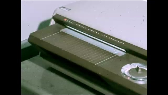 1970s: Close up, hands inserting transparent drawing into machine. Hands holding color scale, clapboard.