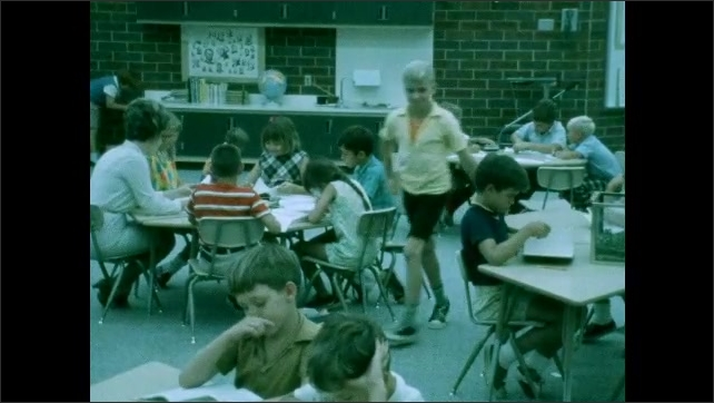 1970s: Woman and kids with slide projector at table, slides on screen. Kids at tables in classroom. Clapboard. Woman looking at book with girl.