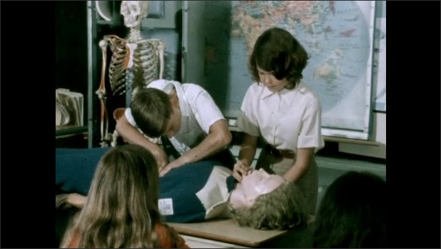 1950s: Boy in classroom. Boy and girl practice CPR on dummy on table at front of class. Boy talks. Boy and girl practice CPR on dummy. Boy adjusts projector showing film in classroom.