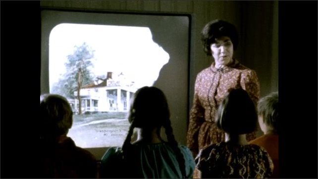 1950s: Person claps film slate. Woman stands in front of projected image on screen talking to kids while pointing at image.