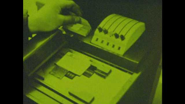 1970s: Person processes credit card transaction. Woman signs receipt. Master Charge. Woman works at computer.
