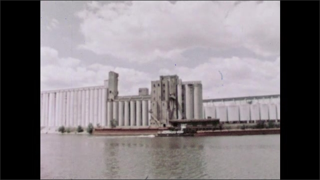 1960s: Man stacks packages into shipping container. River and city. Ship travels along river. Platform tilts vehicle backwards. Grain empties onto grate.