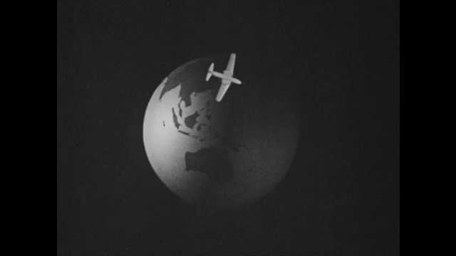 1950s: Model of airplane flying over globe of Earth. Lake at base of mountain.