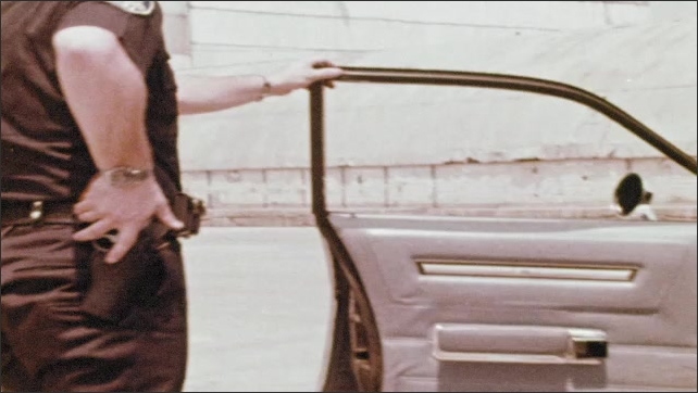 1970s: A police officer opens a car door, braces it with his foot. He exits the vehicle holding onto his pistol in his hip holster. Cop shouts and runs. A cop car drives around a corner.