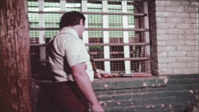 1970s: Hands open a rifle chamber. Man in suit picks up rifle and ammunition cartridge in alley. Man in short sleeves & holster finds gun on windowsill. Hands put on the safety, remove ammunition.