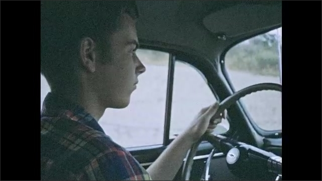 1950s: Driving down road in rain, windshield wipers on. Man drives car. Driving down road in rain. Foot hits pedal. Driving down road.
