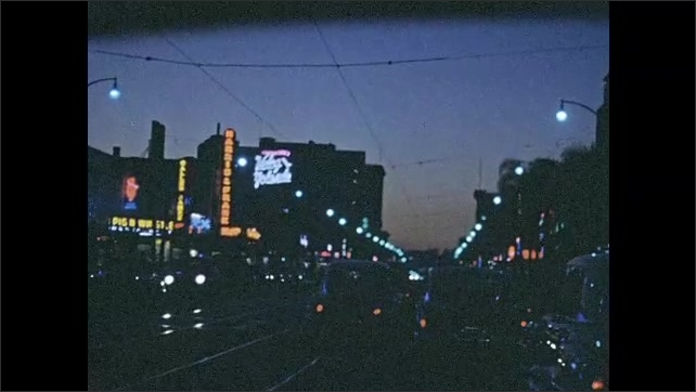 1950s: Driving through city at night, neon lights on buildings.