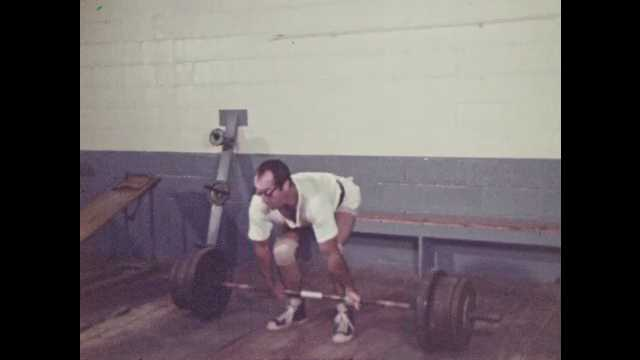 1970s: Man attempts to deadlift weights. Person pulls shop part out of drawer in cupboard.