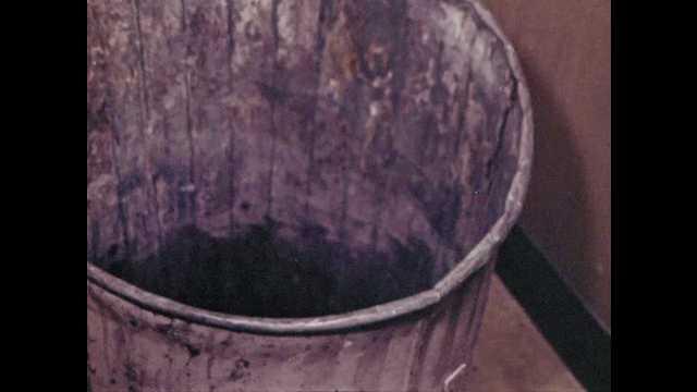 1970s: Trash bin. Person dumps metal shavings into trash. Metal shavings. Saw blade laying out is picked up. Person sweeps metal shavings from counter.