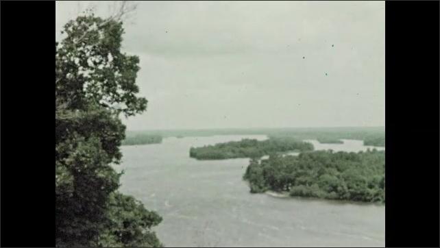1950s: Waves slowly break against rocks. Water flows down mountain creek. River. Man scoops up water in a jar.