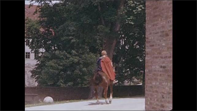 1950s: Panning shot, men riding horseback on street. Man on horse talking to people in field, people salute.