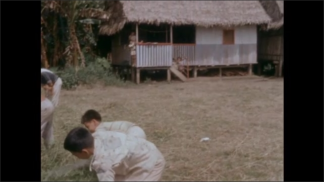 1950s: Person walks across field to people working to clear field. People working in bushes, picking items from ground.