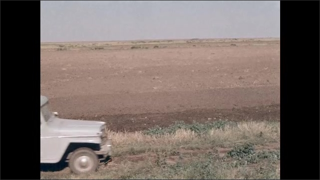 1950s: Truck drives along edge of plowed farm field. Man and boy exit truck. Truck drives past man on tractor. Man on tractor plows field.