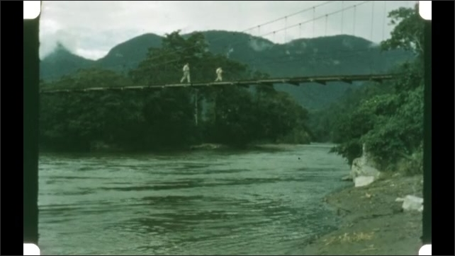 1950s: Pump movement. Men walk across bridge over river. Man walks past sign. Men work in field.