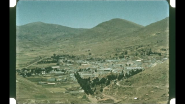 1950s: View of mountains. View of city with mountains in background. People seated in meadow.