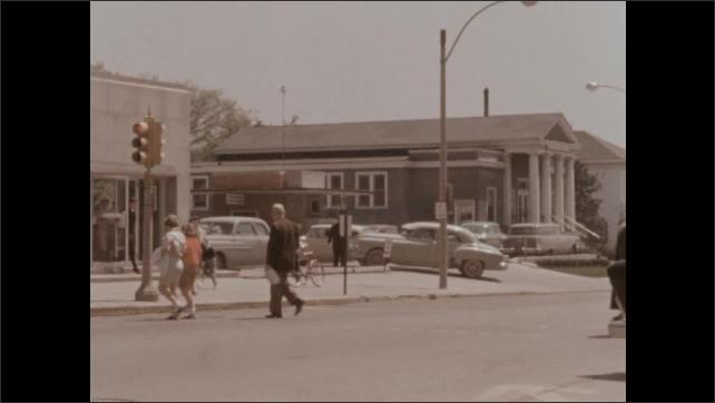1950s: Busy downtown street, stoplight, streetlights, cars pass, stop, pedestrians cross street, children walk with bicycles.
