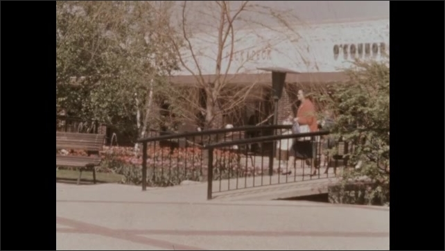 1950s: Garden plaza, tulip beds, low stone wall, planters, shade structures, people stroll through. Building entrance, low bridge, bench, fountain.