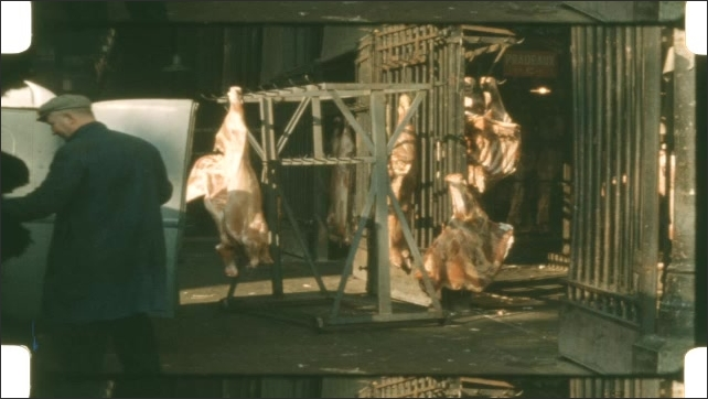 1950s: Racks of meat hang from hooks on shipping dock. Man loads meat into back of van.