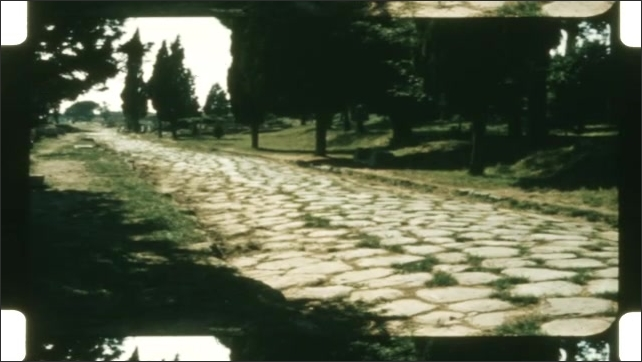 1950s: Boy looks out over ancient ruins, columns lying on ground. Ancient cobblestone road. Historic arch.
