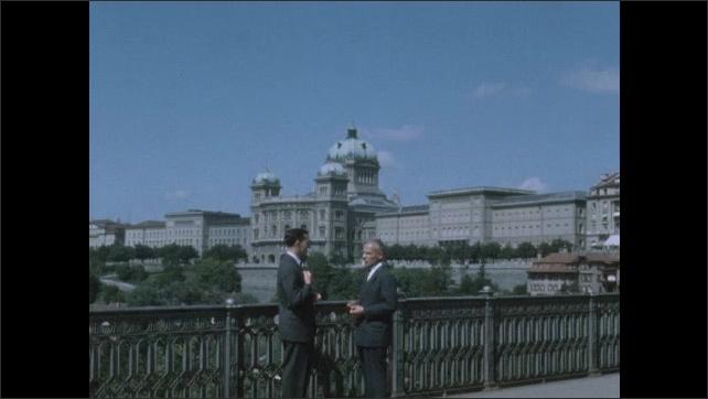 1950s: Men stand on bridge overlooking Geneva and talk.