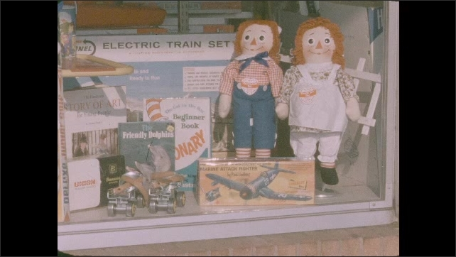 1950s: Toy store window display. Students sit at desks.