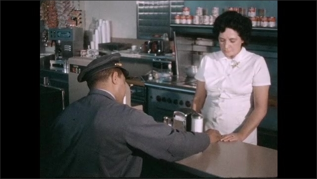 1950s: Man in uniform sits at counter, woman behind counter talks to man. Man gives woman coins. Woman rings up sale.