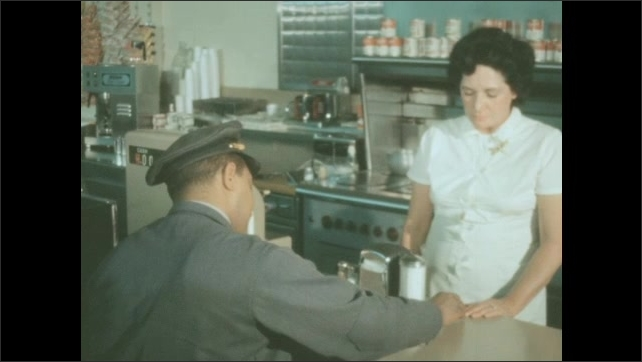 1950s: Postal worker pays for food at diner counter. Waitress counts money and puts it into cash register.