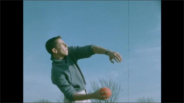 1950s: Man picks up orange ball from grassy field. Man throws ball into the sky. Ball goes into sky and descends.