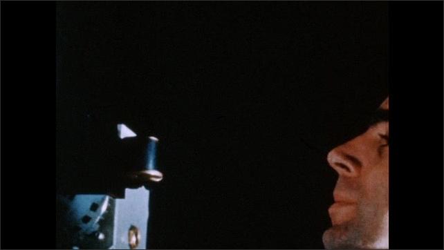 1950s: Man adjusts machine, looks through eyepiece. Man monitors blip on screen, talks.