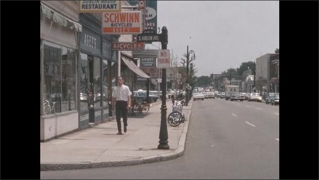 1950s: Traffic sign on side of road, car drives by. People walk down sidewalk in town.