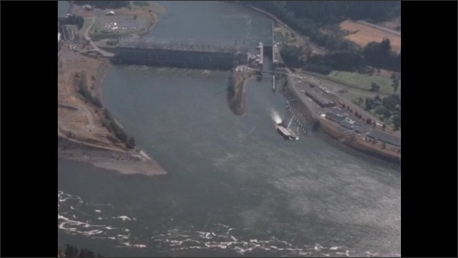 1950s: crane arm rises from water, water drips, crane bottom opens to let out rocky debris onto barge, aerial view of dam with lock system at one side