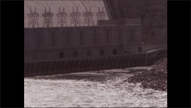 1950s: waves on lake near dam, waves on lake near dam with electrical power plant, transmission towers, rocky shore