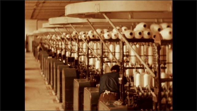 1950s: Weaving machine in textile mill. Rows of machines with man working at one station.