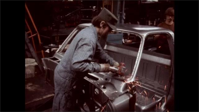 1950s: Factory.  Man pulls car frame along assembly line.  Man uses tool on car.  Men lower body of car onto frame.