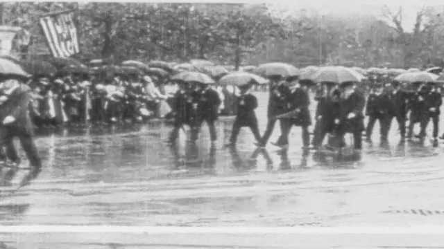 1910s: Men with umbrellas march in parade. Men in suits and horse drawn wagons participate in city parade.