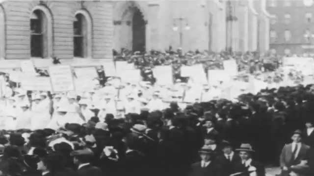 1910s: Crowds watch men and women carry banners and picket signs in city parade.