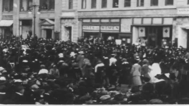 1910s: Spectators watch people carry flags in parade. Crowds watch men and women carry banners and picket signs in city parade.