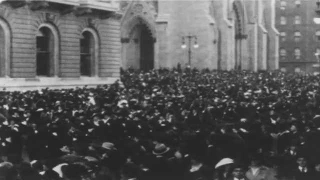 1910s: Marching band parades down city street. Crowds watch men and women carry banners and picket signs in city parade.